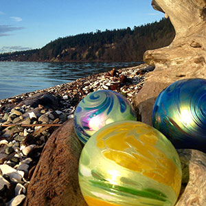 Colorful glass balls rest among the driftwood on a Camano Island beach.