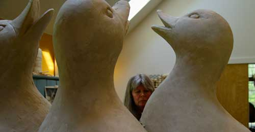 Only Georgia Gerber's head is seen among three giant clay ducks with beaks raised as though singing.