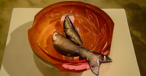 Two glass fish in a glass bowl.