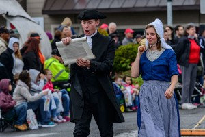 A couple in traditional Dutch clothing walk in the Oak Harbor Holland Happenings Parade.