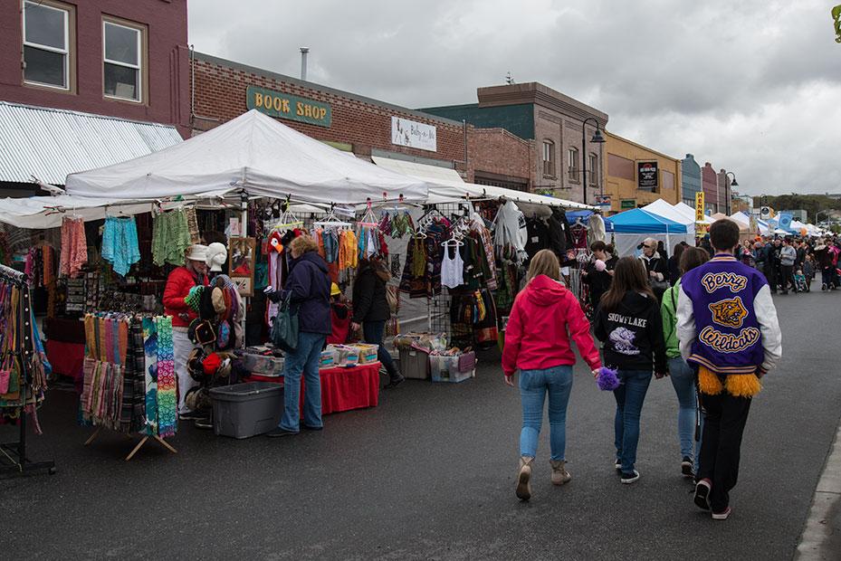 People walk by open air merchants in downtown Oak Harbor