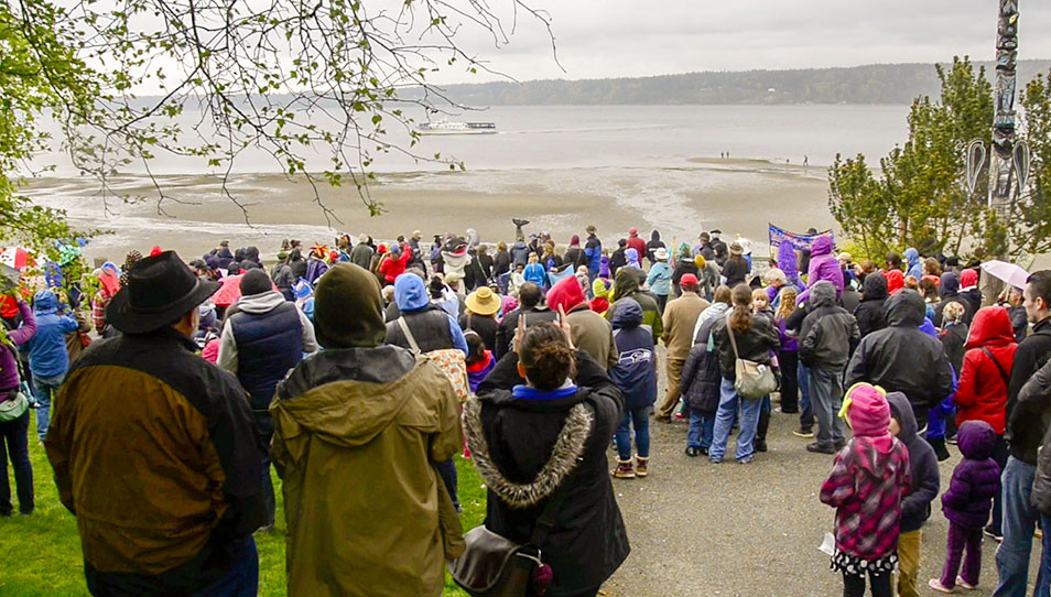 A crowd of people watch the welcoming of the whales on the beach in Langley, Washington.