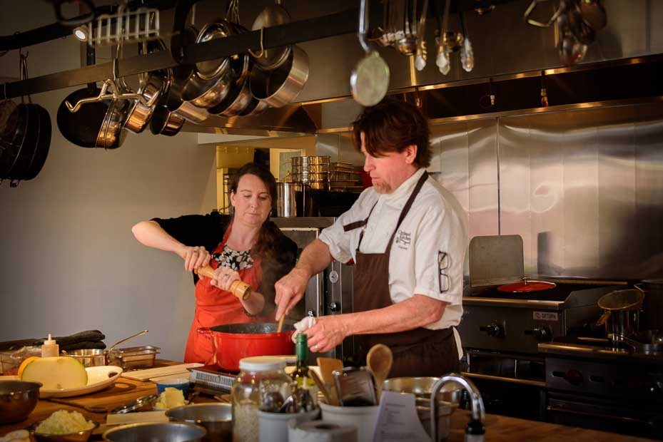 The Orchard Kitchen's Tyla Natress adds salt to a pot wile Vincent Natress stirs.