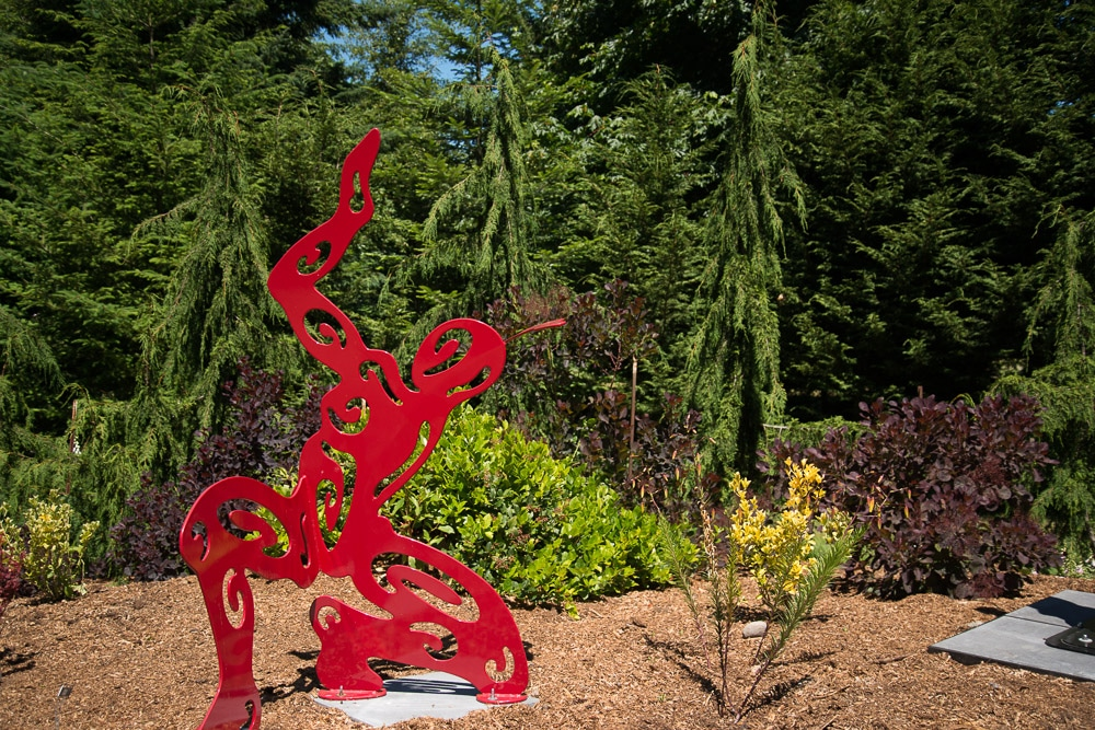 A large somewhat abstract red metal sculpture of a person in an outdoor garden.