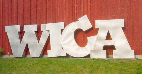 Large metal letters W-I-C-A lean against the side of the Whidbey Island Center for the Arts.