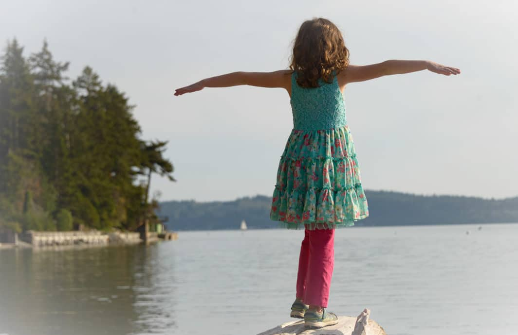 Young Girl standing on a log with her arms outstretched