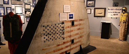The tail section for a military plane with a faded American flag painted on it.