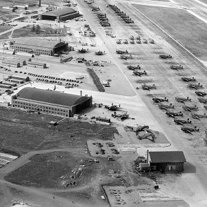 An aerial photo shows several hangers with several dozen airplanes parked outside.