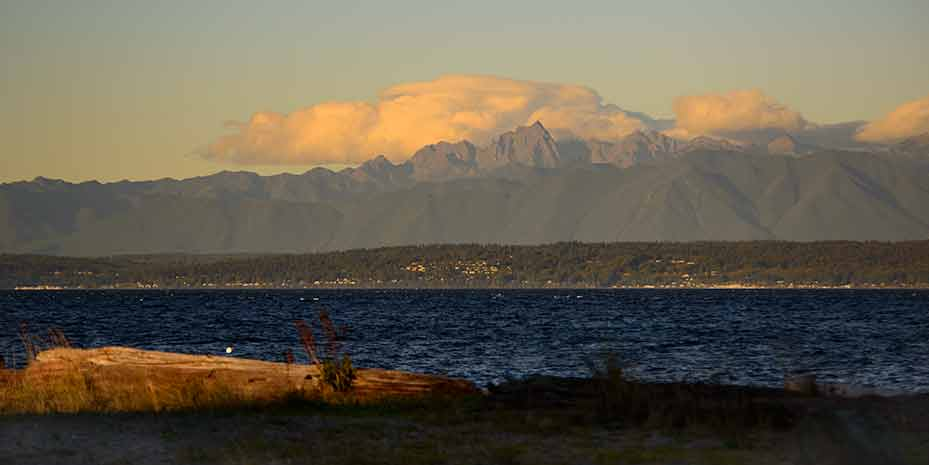 With a dark blue Puget Sound in the foreground, the Olympic Mountains bask in the morning sun.