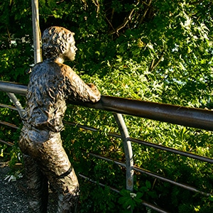 Sculpture of a young boy with arms resting on a railing.