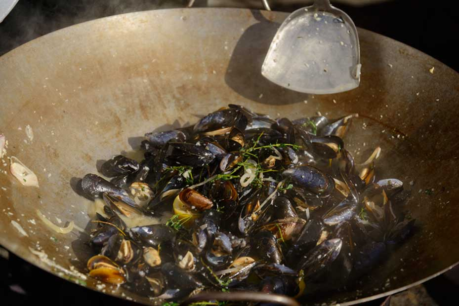 Penn Cove Mussels cooking in a large wok