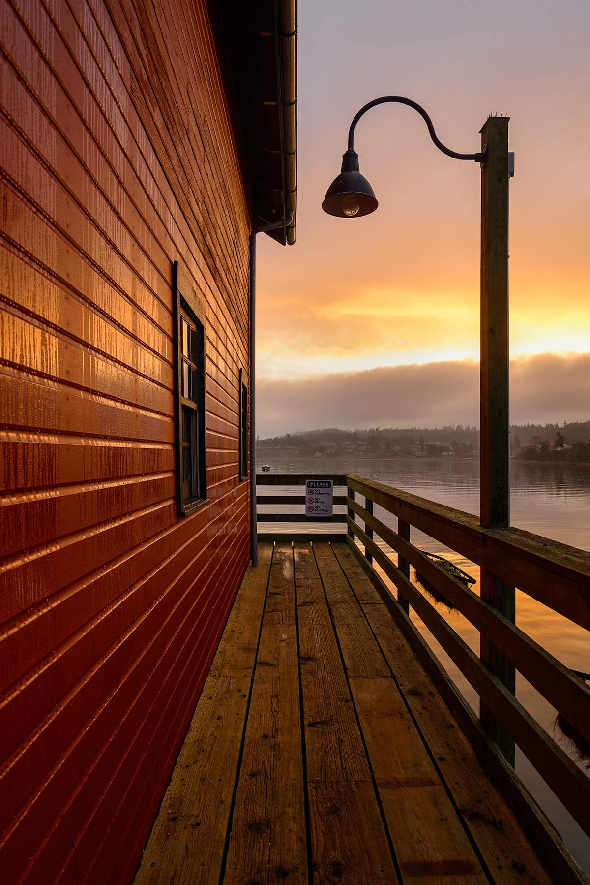 The red walls of the Coupeville Wharf are backed by the oranges of a sunrise.