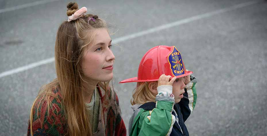 A young woman sits as her son wears a plastic fire helmet and they both watch a concert.