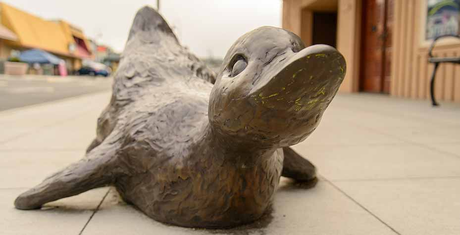 Bronze sculpture of a duck with its feet out from under him