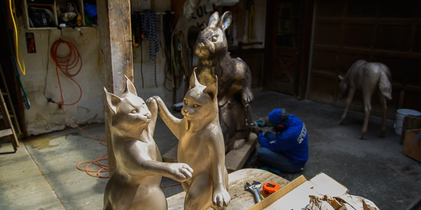Georgia Keck hunches down to work on a statue as other statues are highlighted in the foreground.