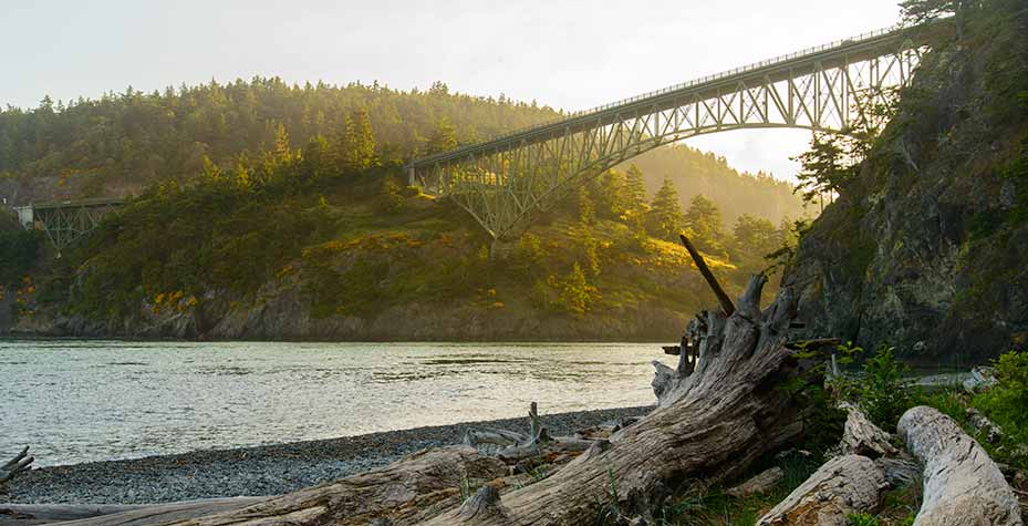 The Deception Pass Bridge towers over the beach as the morning sun lights the bridge from behind.