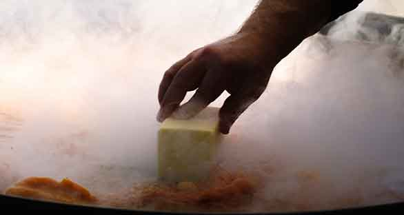 Steam swirls around a hand holding a block of butter in a wok filled with tomato sauce.