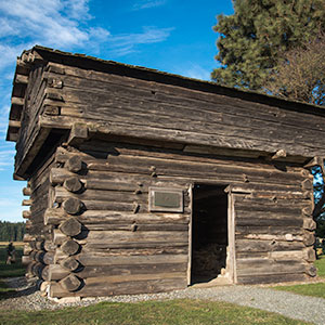 A log cabin with thick walls, tiny windows and a single door sits in a grassy area.