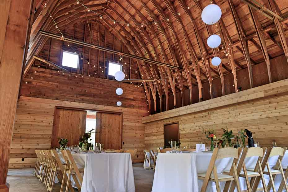 the inside of the barn with tables set up for a party.