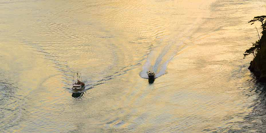 An aerial view of two boats with the sun rising behind them.