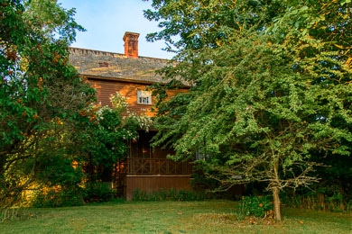 The Haller House is mostly hidden by trees, and the morning sun can only reach a solitary upper-story window.
