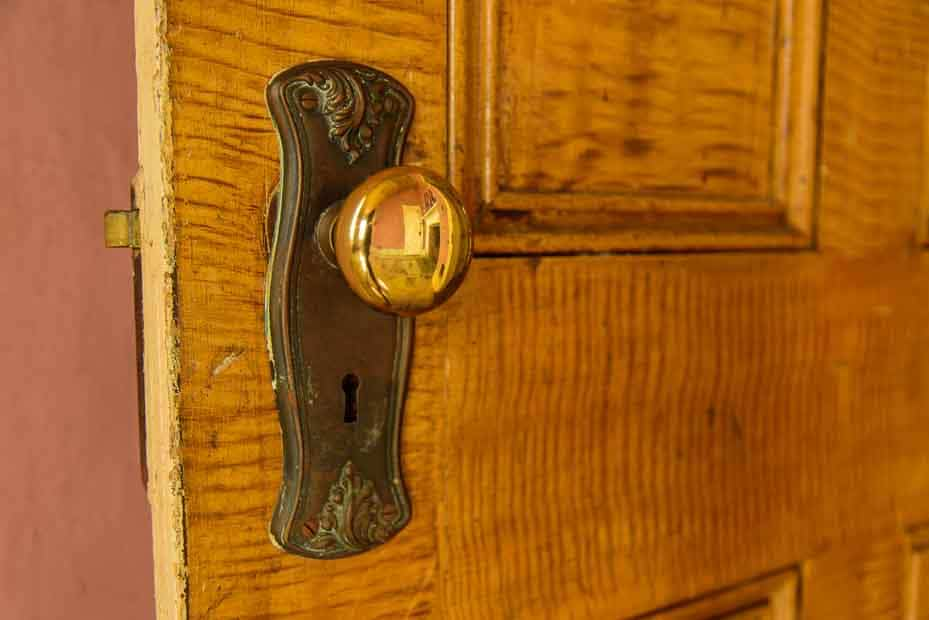 An antique doorknob on a wooden door. The knob, itself, is shiny and reflects the room.