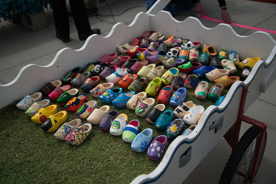 A wooden cart full of miniature decorated wooden shoes.