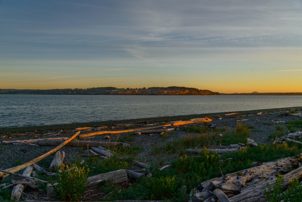 Driftwood on the beach and the mouth of Penn Cove at sunrise.