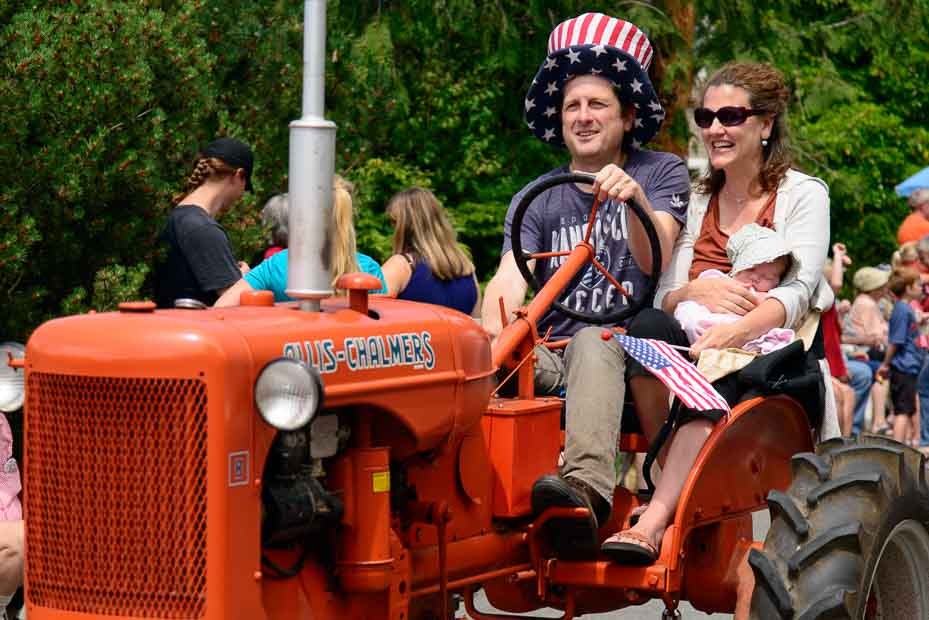 Family of three riding in an old tractor. Dad is wearing a red, white, and blue top hat, and mom is holding a sleeping infant and a small American flag.