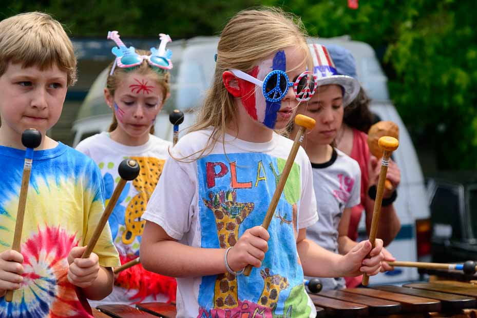 Girl with face painted red, white and blue marches while playing the xylophone in the Maxwelton Independence Day Parade.
