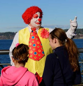 A clown looks into the distance as two children ask him questions.