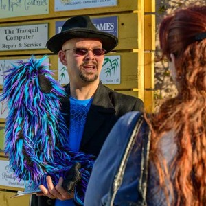 A man in a hat and holding a blue furry puppet answers questions from a woman.