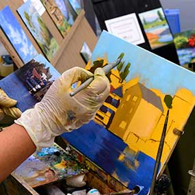 A woman paints a Whidbey Island scene while selling her paintings at the Coupeville Arts Festival.