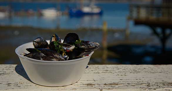 A bowl of mussels sits outside on a railing with Penn Cove in the background.