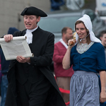 Two people dressed in traditional Dutch clothing walk in the Oak Harbor Holland Happening parade.
