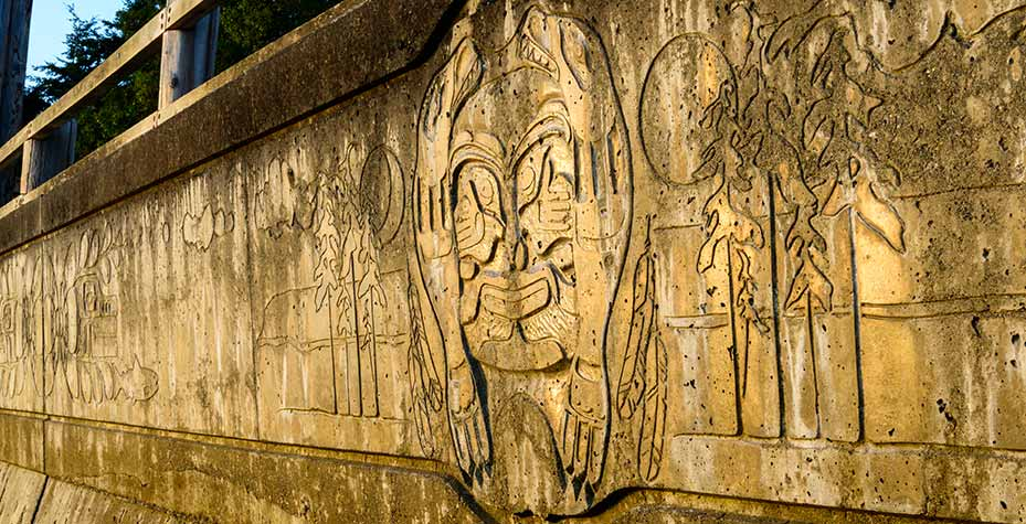 A concrete wall used to protect the bluff from waves is etched with art.