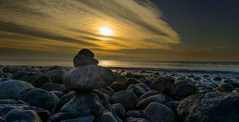 Several smooth piled rocks reach up to a setting sun.