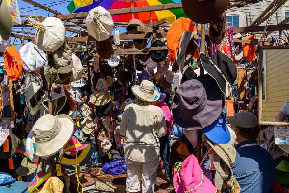 A woman wearing a hat is surrounded by a market stall with dozens of more hats.