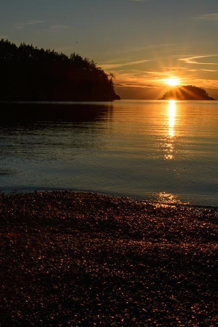 The sun is setting at Bowman Bay. The pebbled bach is in the foreground.
