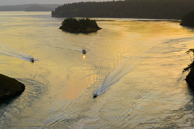 In a view from the Deception pass bridge, there are three boats heading toward the camera. The sun is rising.