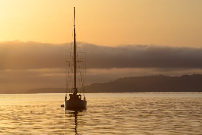 A small sailing boat is at anchor with the sun rising behind it.
