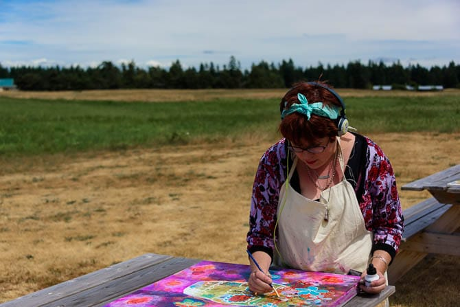 Woman wearing headphones is out in a field painting on a canvas that is on a picnic beanch.