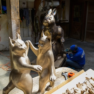 Sculpture of 2 cats (foreground) and woman in work clothes sitting on the floor working on a sculpture (background)