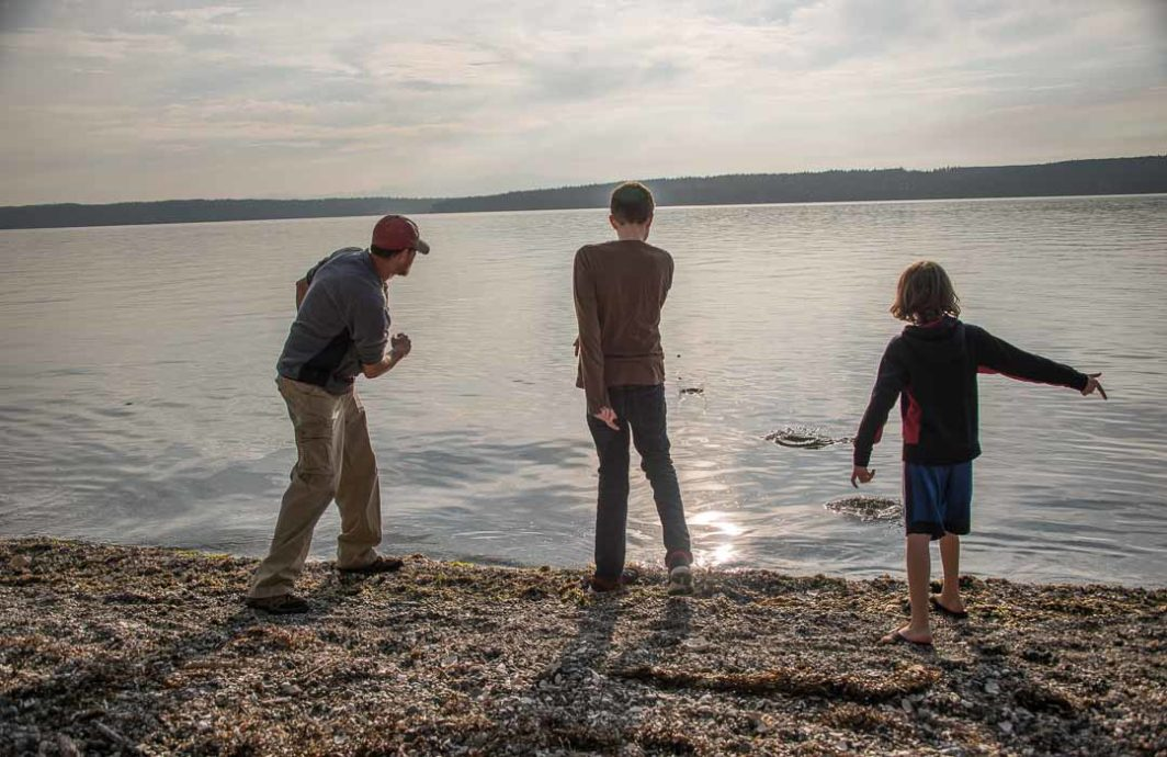 Three people skipping stones into the water