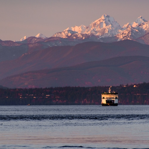 A ferry boat with snow capped mountains in the background