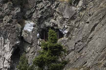 A cave in a cliff with bars across it.