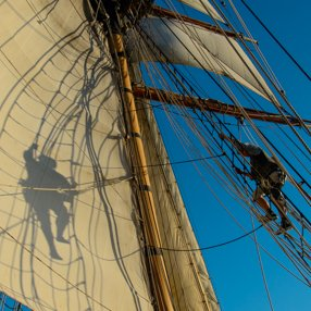 A sailor climbs the rigging of a masted schooner in Penn Cove.  The sailor's shadow is reflected off the sail.