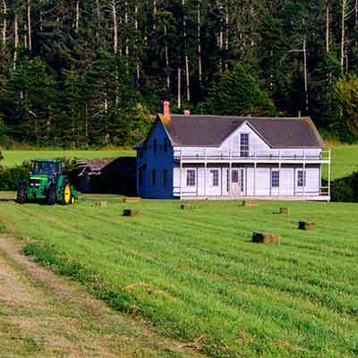 Old house with freshly harvested field around it and a tractor sitting next to the house.