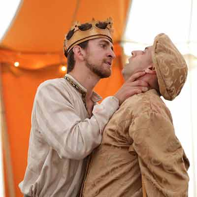 Man wearing a crown grabs another man by the throat.