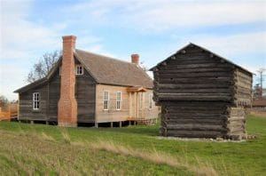 Old wooden house next to a small wooden fortress, a blockhouse